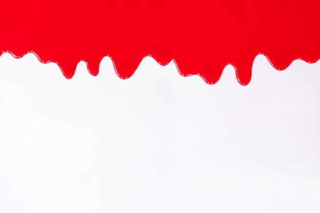 Красная краска капает на белый.