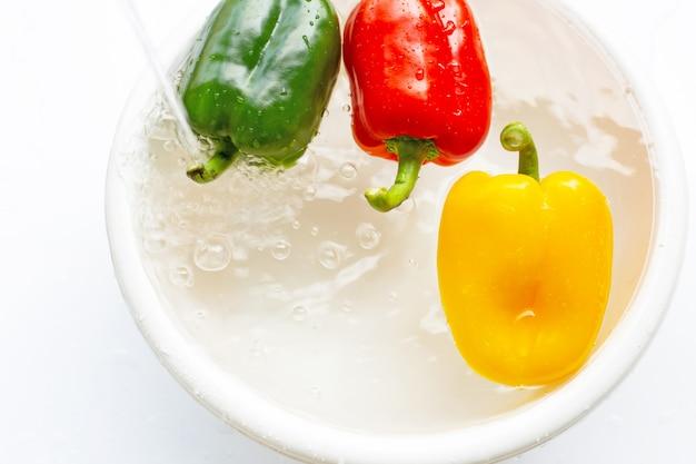 Сладкий перец, смоченный в воде. мыть свежие овощи на белом