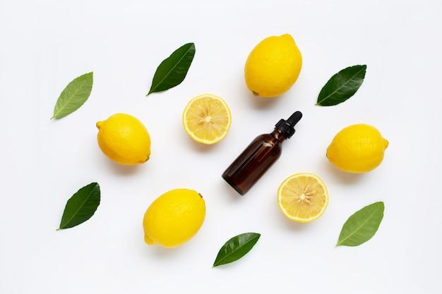 白い背景の上のレモン精油と新鮮なレモン。