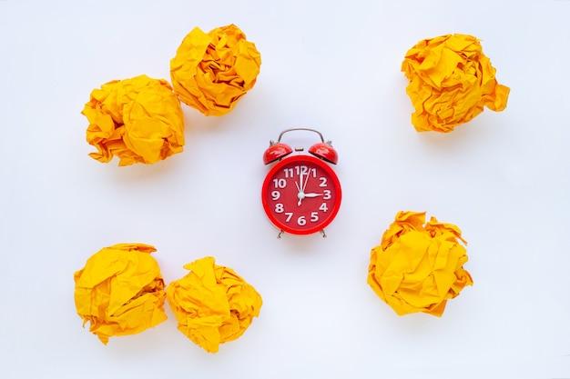 白で隔離される黄色のしわくちゃの紙のボールと赤い目覚まし時計リング
