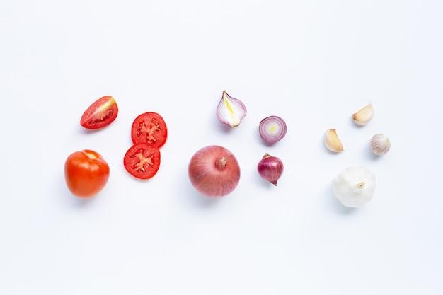 白い背景の上の新鮮な野菜。トマト、赤玉ねぎ、ニンニク、
