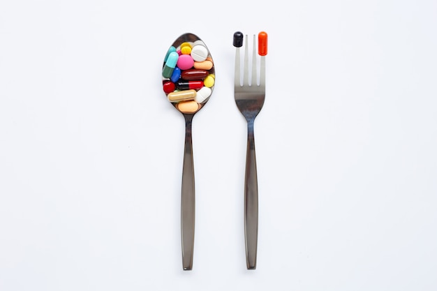スプーンとフォークをカラフルな錠剤、カプセルと白の丸薬