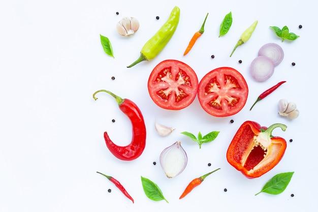 Различные свежие овощи и травы на белом фоне.