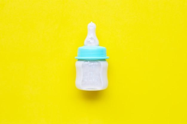黄色の背景に赤ちゃんのための牛乳瓶。