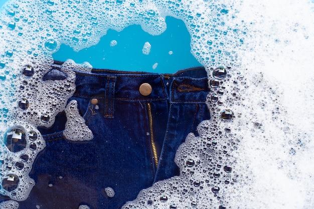 ジーンズは粉末洗剤の水に浸かる。