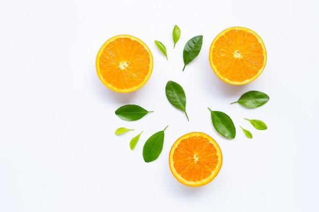 白い表面に分離された葉を持つ新鮮なオレンジ色の柑橘系の果物。