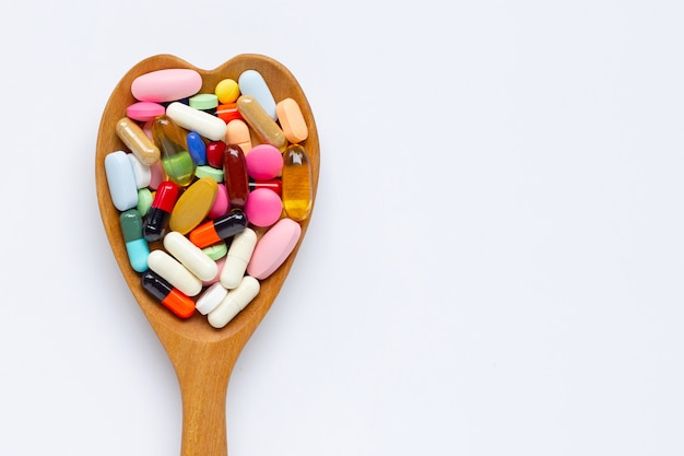 カラフルな錠剤のカプセルと白い背景の上の丸薬。木のハート形のスプーン。