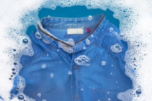 Джинсовую рубашку замочить в порошке моющего средства для растворения воды. концепция прачечной