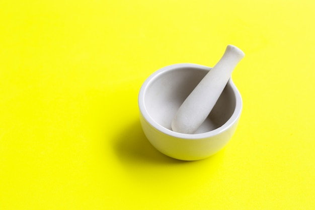 乳鉢と乳棒の緑の黄色の背景。