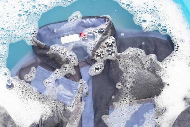 シャツは、粉末洗剤の水に浸します。ランドリーのコンセプト