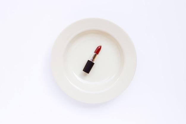 Губная помада на белом блюде на белизне.