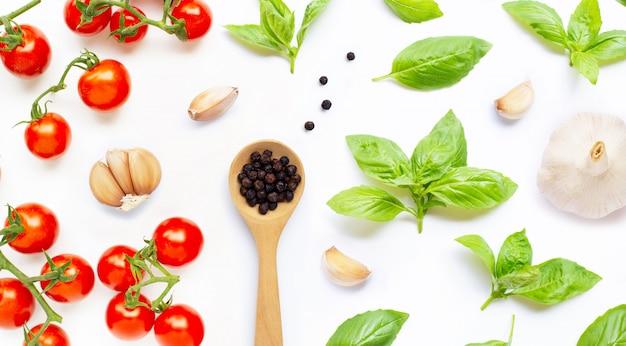 Свежие помидоры черри с чесноком, черным перцем и листьями базилика на белом