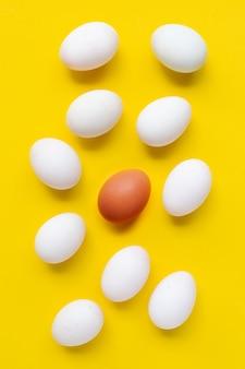 Свежие яйца на желтой поверхности.