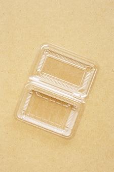 合板の背景にプラスチック製の食品容器。