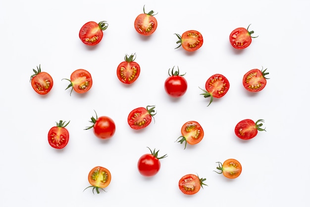 Свежие помидоры, целые и половинки, изолированные на белом