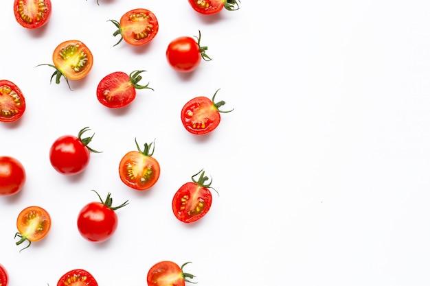 Свежие помидоры черри, целые и половинки, изолированные на белом