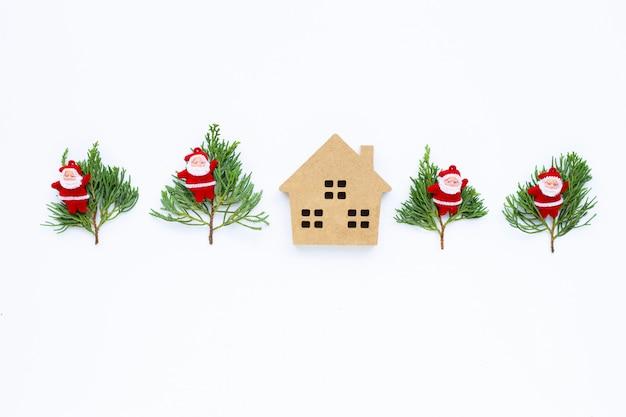 メリークリスマスとハッピーホリデー、クリスマス組成のミニチュアの家。ギフト、松の枝、白の装飾