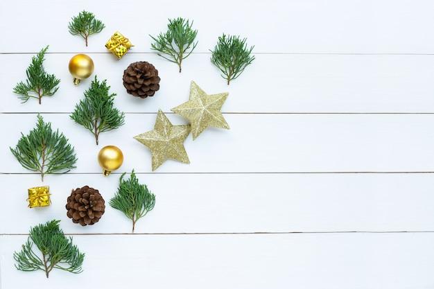メリークリスマスとハッピーホリデー、クリスマス組成。金色の星、松の枝、白い木製の背景の装飾。