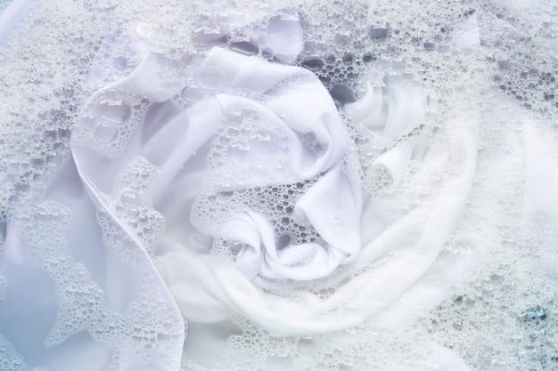 白い服を粉末洗剤の水に浸してください。ランドリーのコンセプト