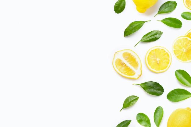 Свежий лимон с зелеными листьями на белом фоне