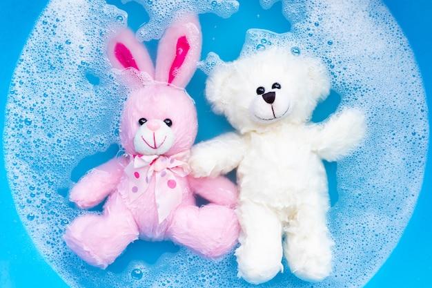 洗う前に、ウサギの人形をテディベアのおもちゃで洗濯洗剤の水に浸します。