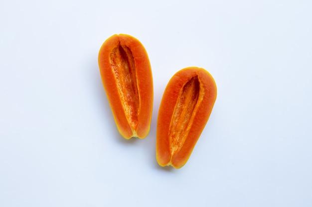 白い背景に熟したパパイヤの果実の半分、種子を削除