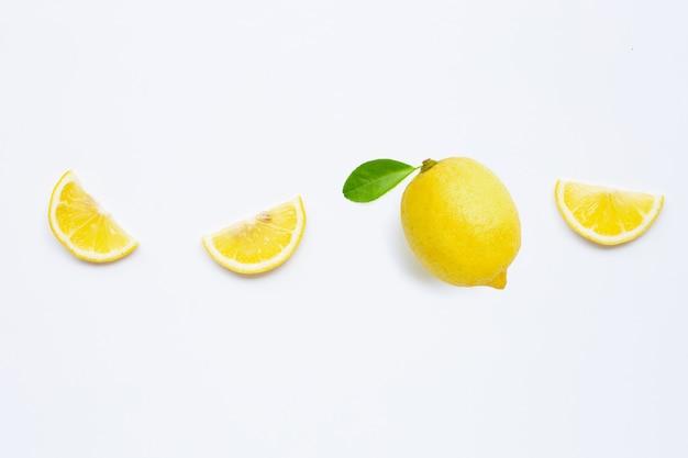 Свежий лимон с зелеными листьями на белом