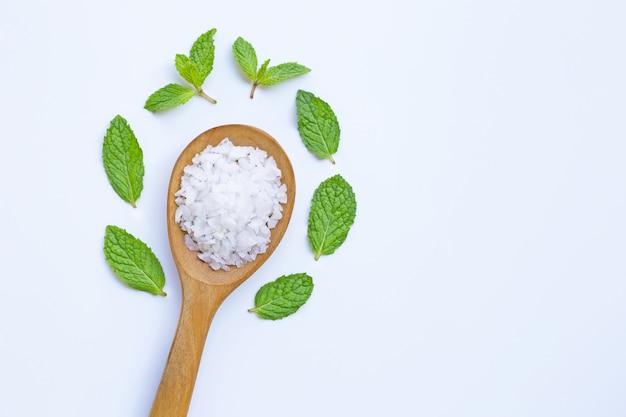 白い背景に新鮮なミントと木製スプーンの塩
