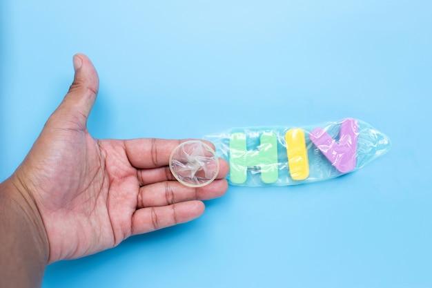 Рука с «вич» красочный алфавит в презервативе на синем фоне. сохранить концепцию секса