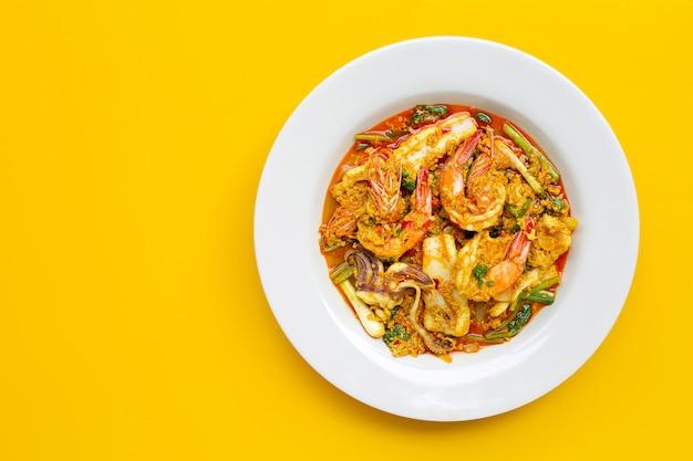 Жареные морепродукты с карри на желтом фоне.