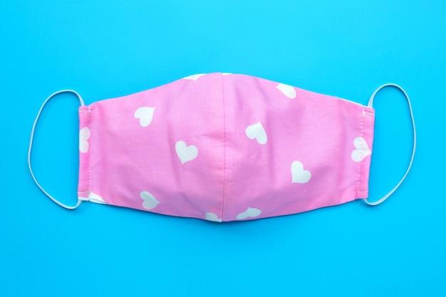 青の背景に白いハートのマスクで手作りのピンクの布。上面図