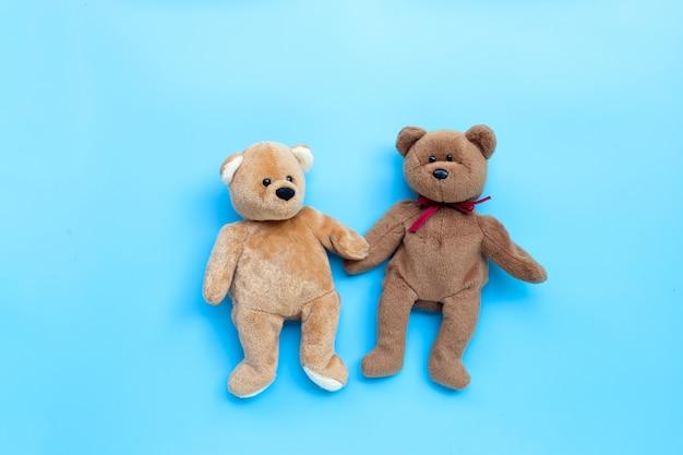 青色の背景におもちゃのカップルを負担します。