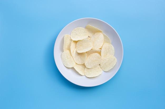 Картофельные чипсы на синем фоне.