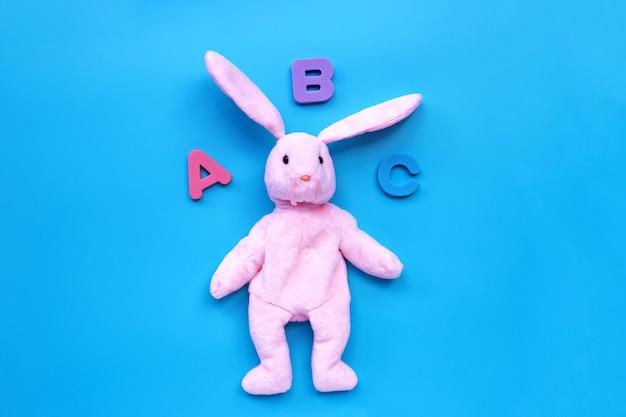 青の背景に英語のアルファベットとウサギのおもちゃ。教育コンセプト、コピースペース