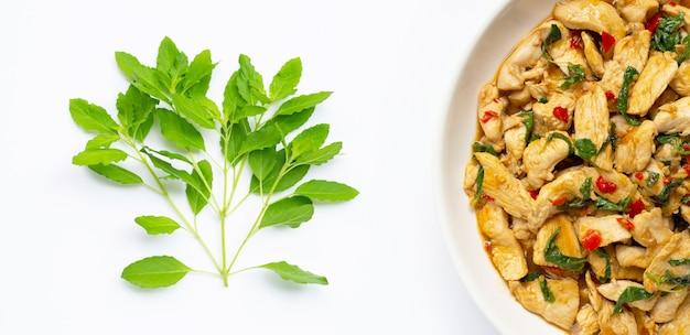 Святой базилик листья и блюдо из жареной курицы с базиликом на белом
