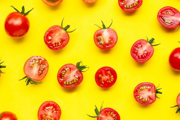Свежие томаты, весь и неполная вырубка изолированные на желтой предпосылке.