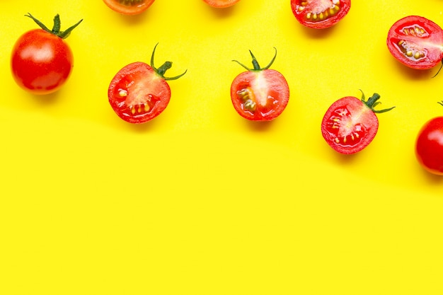 Свежие помидоры черри, целые и неполной вырубки, изолированные на желтом фоне.