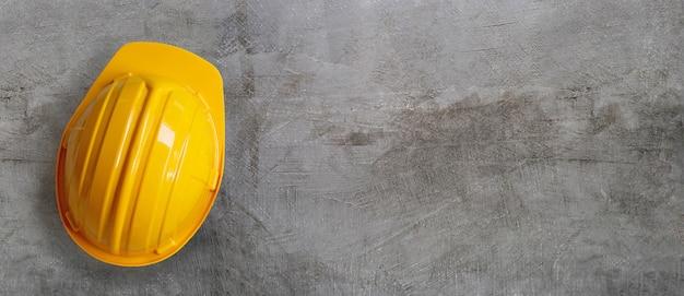 Каска строительная на бетонном фоне.