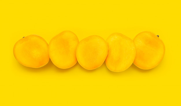 Тропический фрукт, манго ломтики на желтом фоне.