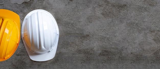 Строительные каски на бетонном фоне.