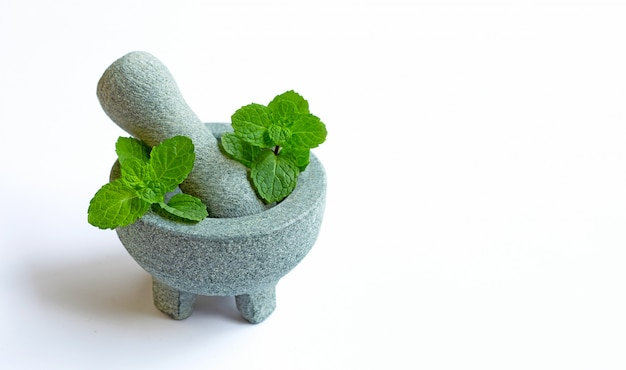 石造り乳鉢と乳棒の白い背景の上のミントの葉。