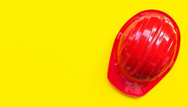 Красный строительный шлем на желтом фоне.