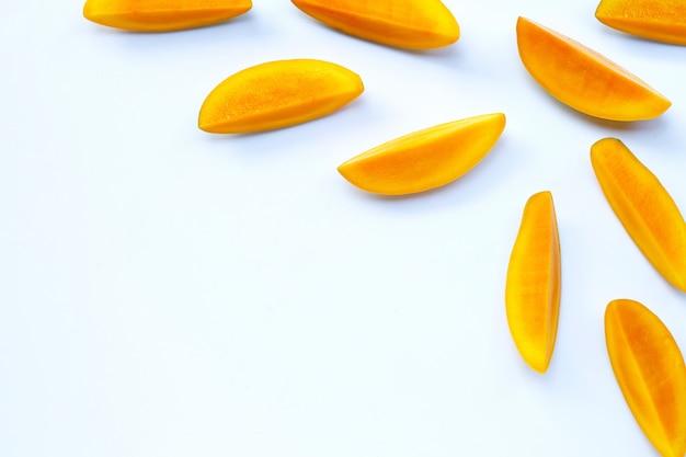 Тропический фрукт, кусочки манго на белой поверхности.