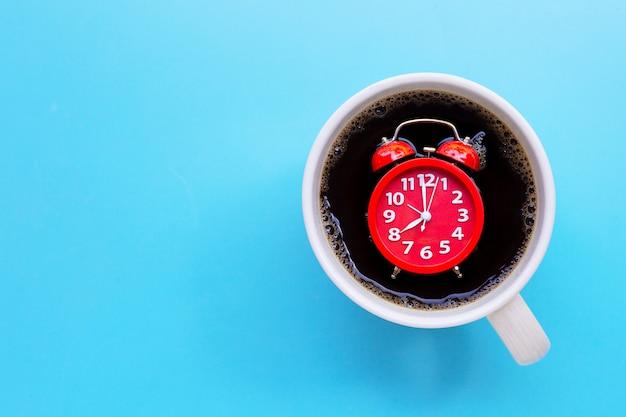 青の背景にコーヒーカップの赤い目覚まし時計。