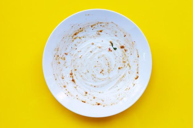 黄色の背景に汚れた皿。