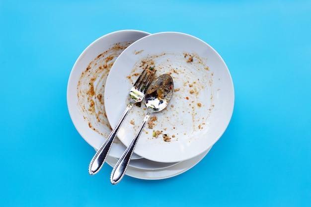 青色の背景に汚れた皿。