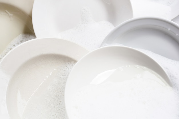 食器洗い、台所の流しに浸した汚れた皿。