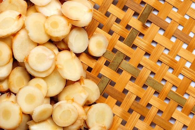 Свежие ломтики галангала на деревянной бамбуковой обмолоте