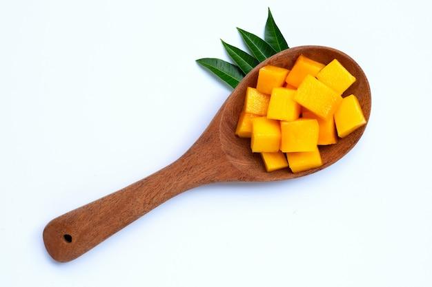 Нарезанные спелые манго кубики на деревянной ложкой на белом