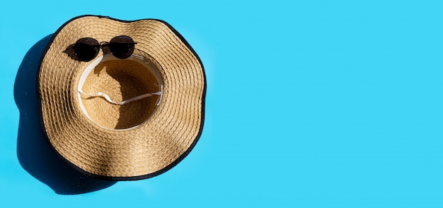 Шляпа и солнцезащитные очки на синем фоне. наслаждайтесь концепцией летнего отдыха.